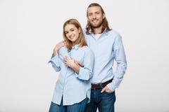 Портрет жизнерадостных молодых пар стоя и обнимая один другого на изолированной белой предпосылке Стоковое фото RF