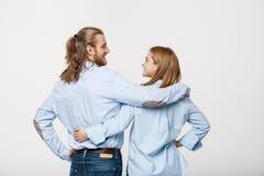 Портрет жизнерадостных молодых пар стоя и обнимая один другого на изолированной белой предпосылке Стоковое Изображение RF