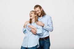 Портрет жизнерадостных молодых пар стоя и обнимая один другого на изолированной белой предпосылке Стоковые Фотографии RF