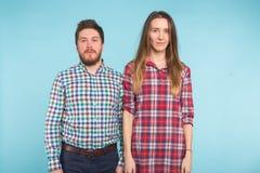 Портрет жизнерадостных смешных молодых любовников околпачивая вокруг на голубой предпосылке стоковые фото