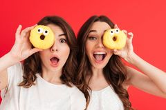 Портрет 2 жизнерадостных счастливых девушек представляя с donuts Стоковые Фотографии RF