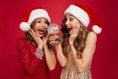 Портрет 2 жизнерадостных усмехаясь женщин в шляпах рождества Стоковые Изображения RF