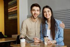 Портрет жизнерадостных startupers перспективы спаривает с темными волосами в вскользь одеждах, сидящ в кафе, усмехаться яркий Стоковое Фото
