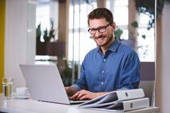 Портрет жизнерадостного бизнесмена работая на компьтер-книжке на творческом офисе Стоковое фото RF