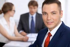 Портрет жизнерадостного усмехаясь бизнесмена против группы в составе бизнесмены на встрече Стоковое Изображение RF