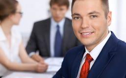 Портрет жизнерадостного усмехаясь бизнесмена против группы в составе бизнесмены на встрече Стоковые Фото