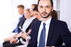 Портрет жизнерадостного усмехаясь бизнесмена против группы людей на встрече Стоковое Изображение RF