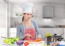 Портрет жизнерадостной варя женщины в кухне Стоковые Фотографии RF