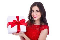 Портрет жизнерадостной женщины в красном платье с подарочной коробкой изолировал o Стоковые Фото