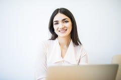 Портрет жизнерадостной коммерсантки сидя на таблице в офисе и смотря камеру Стоковые Изображения RF
