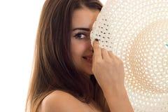 Портрет жизнерадостной молодой девушки брюнет с соломенной шляпой в ее руках усмехаясь на камере изолированной на белой предпосыл Стоковые Изображения RF
