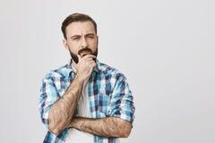 Портрет заботливого бородатого взрослого человека, с серьезным выражением, пересекая рукой и держать другие на подбородке пока стоковое изображение
