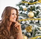 Портрет заботливой женщины сидя около рождественской елки Стоковые Фото