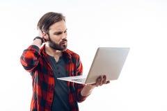 Портрет задумчивого бородатого грустного ноутбука удерживания Гай стоковая фотография