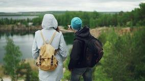 Портрет замедленного движения 2 туристов друзей наслаждаясь взглядом от горы, молодой человек указывает на визирования с его сток-видео