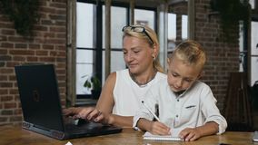 Портрет занятой красивой средн-достигшей возраста бизнес-леди работая на ноутбуке когда ее маленький прекрасный внук что-то видеоматериал