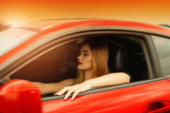 Портрет захода солнца молодой красивой девушки управляя автомобилем Стоковые Изображения