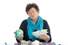 Портрет: Задумчивая более старая дама думая о праздниках - жулик денег стоковое фото