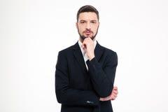Портрет задумчивого бизнесмена смотря камеру Стоковые Фото