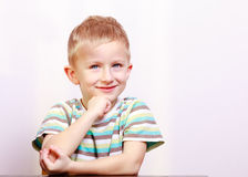 Портрет задумчивого усмехаясь белокурого ребенк ребенка мальчика на таблице Стоковые Изображения RF