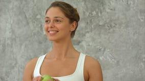 Портрет здоровой женщины с яблоком, говоря и усмехаясь Стоковое Изображение