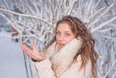 Портрет зимы женщины в белом пальто во время снежностей в парке Стоковое Изображение RF