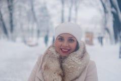 Портрет зимы женщины в белом пальто во время снежностей в парке стоковые изображения rf