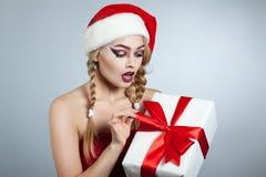 Портрет зимы женщины в shlyayape santa Подарочная коробка с красным полетом в его руки взволнованности людские Стоковая Фотография RF