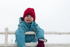 Портрет зимы мальчика в красной шляпе младенец усмехается стоковое фото