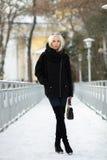 Портрет зимы: молодая белокурая женщина одела в ботинках голубых джинсов теплых шерстяных куртки длинных представляя снаружи в сн Стоковое фото RF
