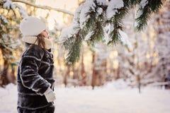 Портрет зимы прелестной девушки ребенка дуя на снеге на ветви ели в лесе Стоковое Изображение