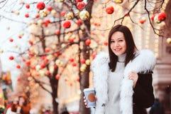 портрет зимы счастливой молодой женщины идя в улицы города рождества стоковое фото
