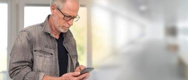 Портрет зрелого человека используя его телефон, световой эффект Стоковые Изображения RF