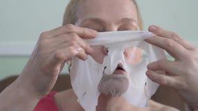 Портрет зрелой женщины в лицевой маске для стороны Косметическая забота кожи процедуры Концентрация эмоции выбора r сток-видео