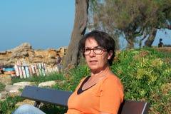 Портрет зрелой женщины с eyeglasses, сидя на стенде Стоковая Фотография RF