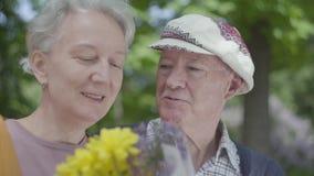 Портрет зрелой пары в любов сидя на стенде в парке Взрослая женщина и ее пожилой супруг обнюхивая a акции видеоматериалы