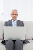 Портрет зрелого бизнесмена используя компьтер-книжку на софе Стоковые Фотографии RF