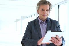 Портрет зрелого бизнесмена используя цифровую таблетку в новом офисе Стоковая Фотография RF