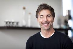 Портрет зрелого красивого человека усмехаясь на камере дом стоковые фото