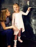 Портрет зрелого учителя женщины с маленьким милым белокурым сочинительством зрачка девушки на классн классном совместно, люди обр Стоковое фото RF