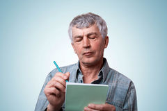 Портрет зрелого человека при рубашка демикотона серых волос нося стильная держа тетрадь и ручку в его руках делая некоторые приме Стоковые Изображения