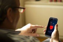 Портрет зрелого человека с здоровьем app на мобильном телефоне Стоковое Фото