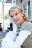 Портрет зрелой усмехаясь белокурой женщины перед домом Стоковое фото RF