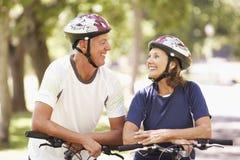 Портрет зрелых пар на езде цикла через парк стоковое изображение rf