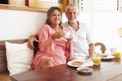 Портрет зрелых пар сидя на таблице завтрака Стоковые Изображения