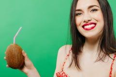Портрет зубастой усмехаясь молодой женщины выпивая тропический коктеиль в кокосе и смотря камеру на зеленом цвете Стоковое Изображение