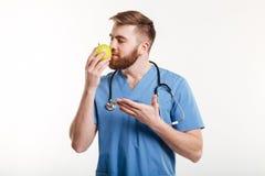 Портрет здорового доктора пахнуть яблоком и указывать Стоковые Фотографии RF