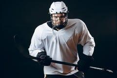 Портрет игрока хоккея на льде с хоккейной клюшкой и шайбы изолированной над чернотой стоковые изображения rf