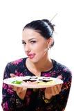 Портрет лизать молодую женщину губ красивую имея потеху сидя на таблице и держа плиту суш стоковые изображения rf
