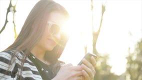 Портрет изумительной молодой женщины с Smartphone и солнечными очками Outdoors Милое брюнет используя ее мобильный телефон с сток-видео
